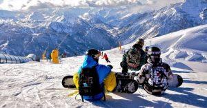 Snowboarders sulla neve delle piste